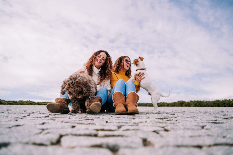 Smiling women playing with dog sitting against sky