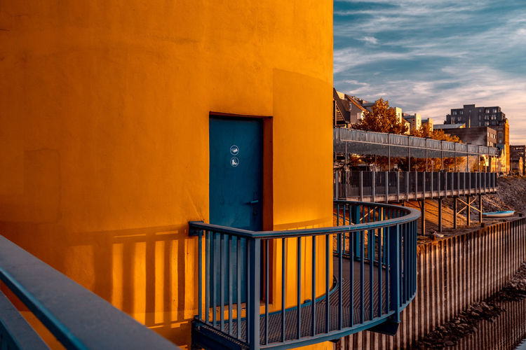 Yellow door by building against sky