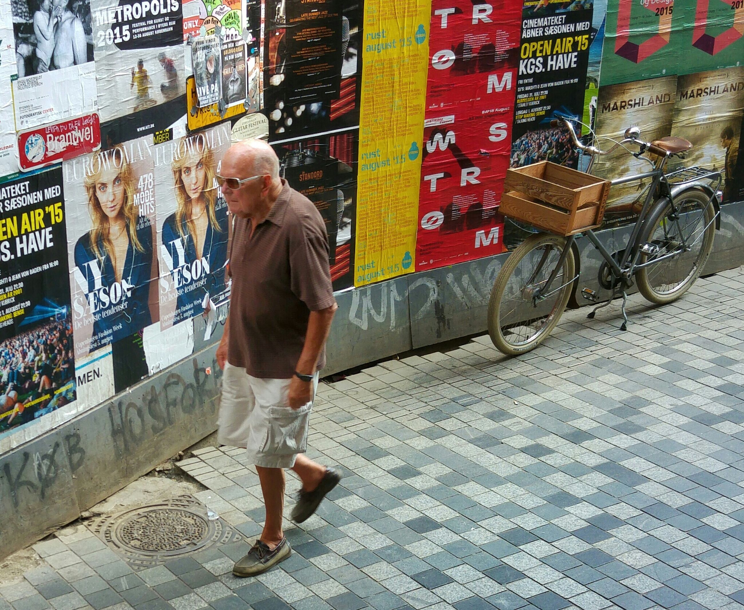 full length, lifestyles, casual clothing, text, street, graffiti, leisure activity, wall - building feature, built structure, architecture, childhood, sidewalk, building exterior, day, outdoors, walking, standing, boys