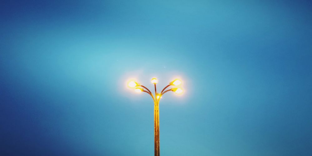Low angle view of illuminated street light against blue sky