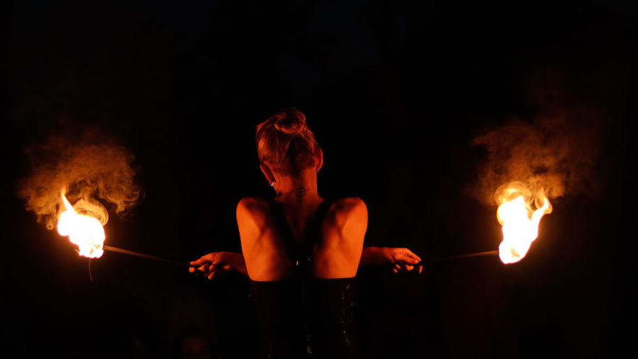 Rear view of woman doing fire stunt night