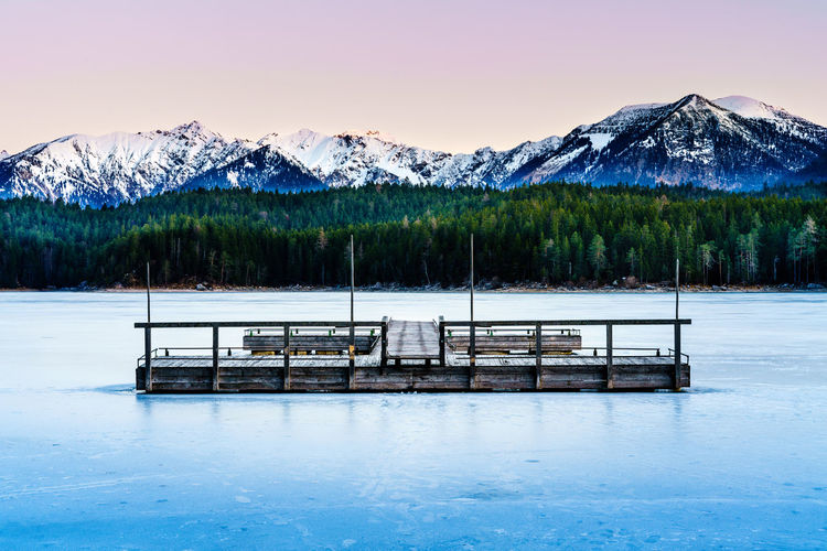 Wooden pontoon on frozen Eibsee in late winter in South Bavaria, Germany Outdoors No People Tranquility Snow Nature Water Mountain Range Cold Temperature Beauty In Nature Frozen Ice Wooden Deck Lake Isolated Sunrise Winter Forest Blue Purple Pastel Mountain Scenics - Nature Snowcapped Mountain Non-urban Scene