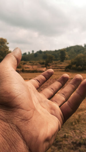 Cropped image of man hand against cloudy sky