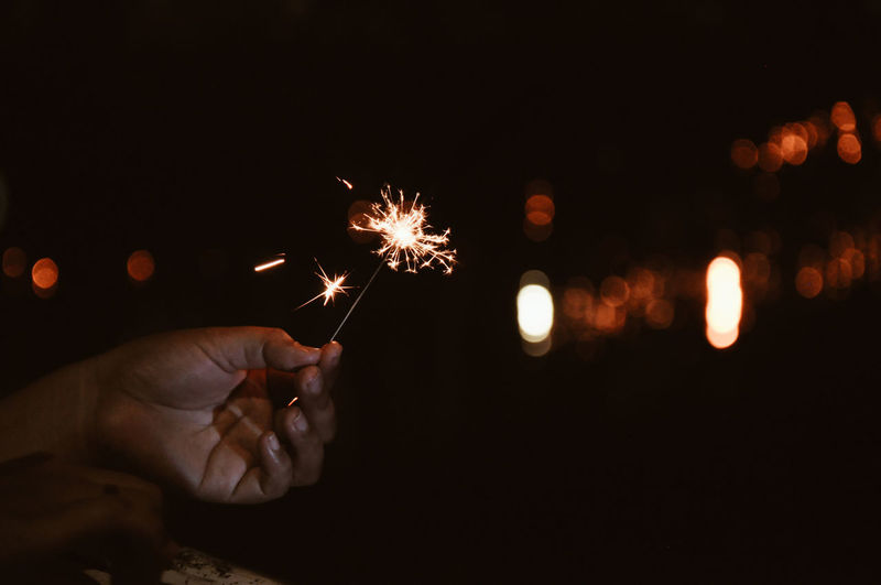 Close-up of hand holding illuminated sparkler at night