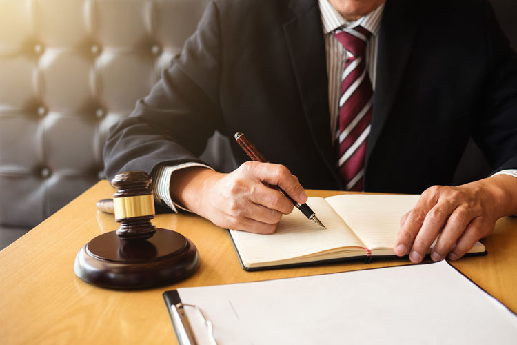Midsection of lawyer working on desk at office