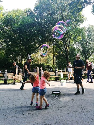 Large Group Of People Bubble Wand Playing Full Length Togetherness Childhood Mid-air Fun Leisure Activity Girls Day Motion Real People Tree Standing Boys People Outdoors Child Friendship Adult Chilren Activity Playtime