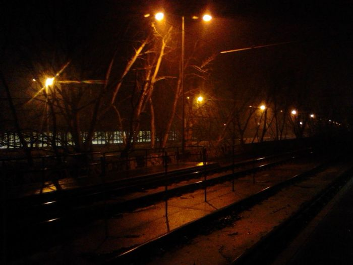 Illuminated street by railroad tracks in city against sky at night