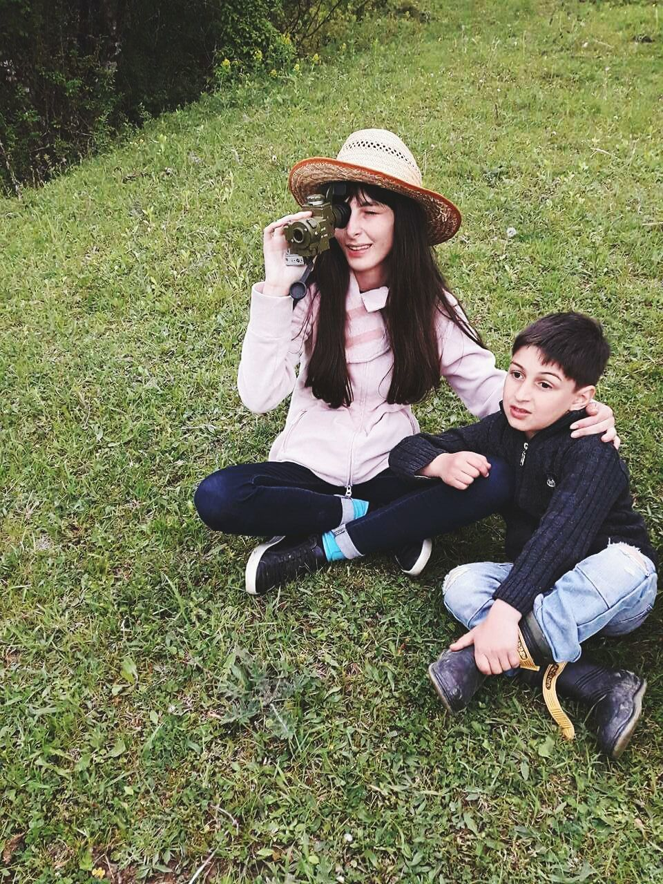 two people, real people, hat, casual clothing, full length, togetherness, lifestyles, leisure activity, grass, smiling, sitting, happiness, young women, teenage girls, young adult, day, women, outdoors, friendship, girls, wireless technology, bonding, childhood, nature, technology, beauty in nature, people