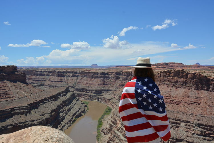 Rear view of woman wrapped in flag standing on mountain