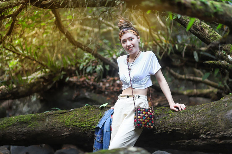 Portrait of smiling young woman standing by log in forest