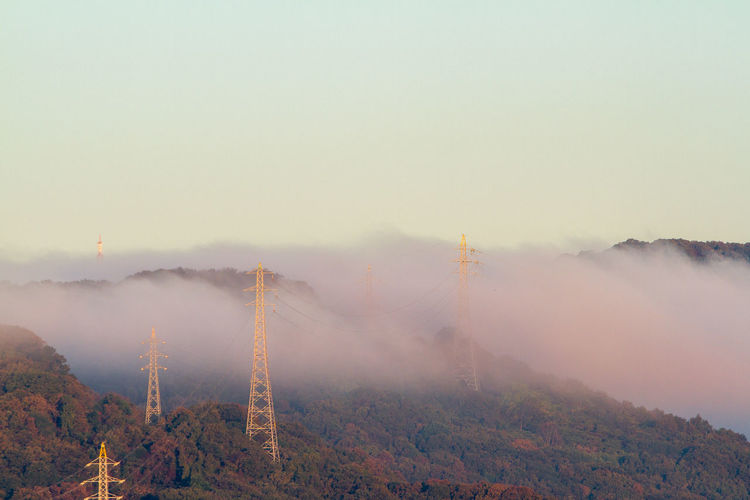 Electricity Pylons On Mountains In Foggy Weather
