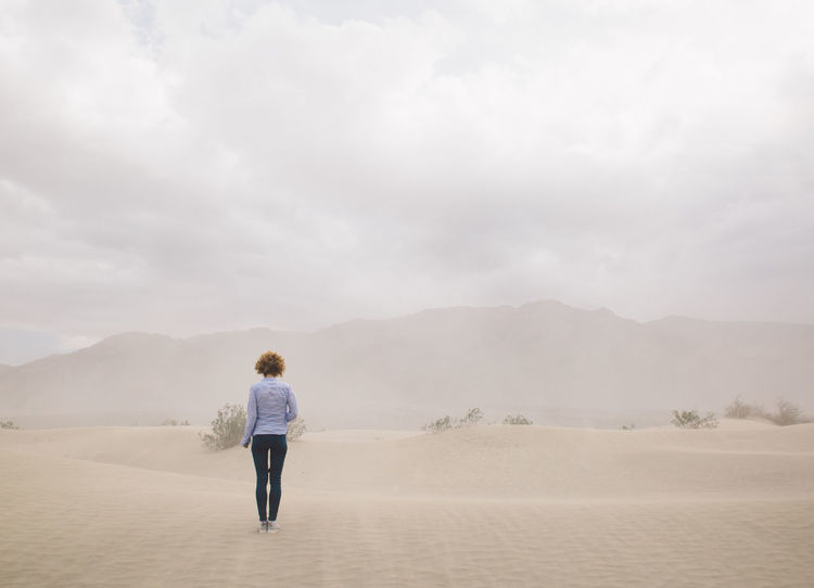 Arid Climate Arid Landscape Casual Clothing Curly Hair Day Death Valley Death Valley National Park Desert Desert Dunes Full Length Girl Landscape Leisure Activity Nature One Person Outdoors Real People Rear View Sand Sand Dune Sand Storm Sky Standing Storm The Great Outdoors - 2017 EyeEm Awards