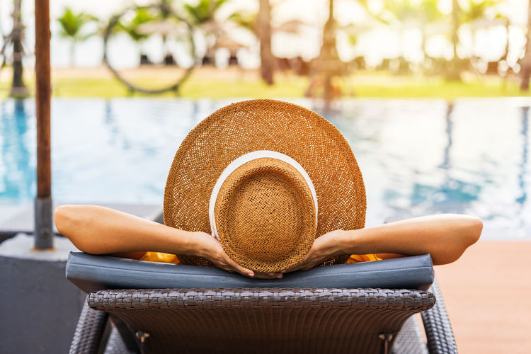 Woman sitting on chair by swimming pool