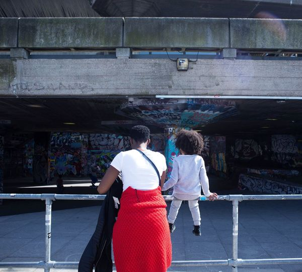 Rear view of mother and daughter at railing against building