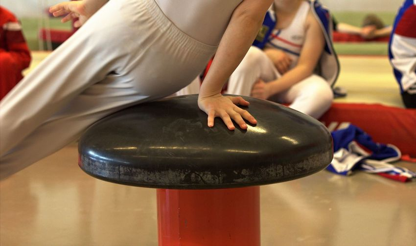 Midsection of child balancing on equipment in gymnastics class