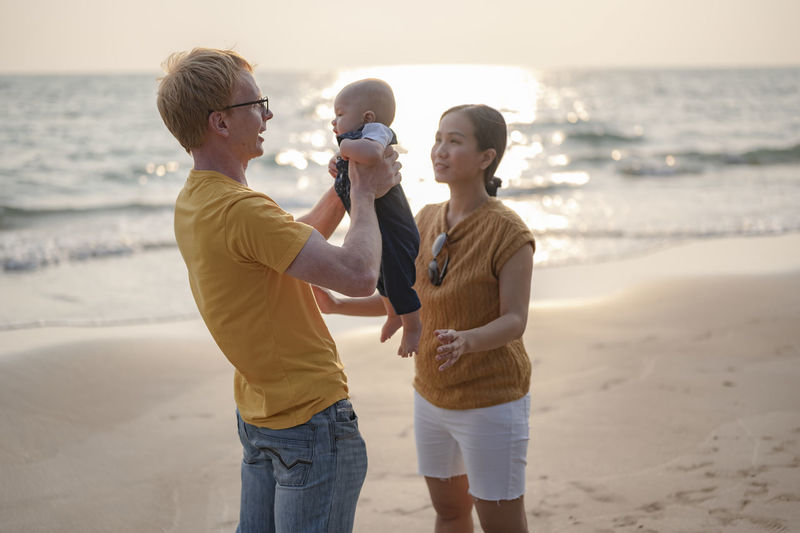 Cheerful family standing on beach with baby against sky