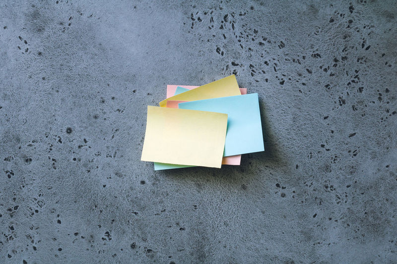 Close-up of stacked adhesive notes on wall