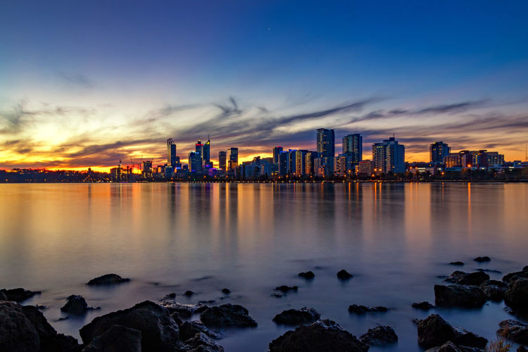 Beautiful view of city at sunset Architecture Bay Building Building Exterior Built Structure City Cityscape Cloud - Sky Illuminated Landscape Nature No People Office Building Exterior Outdoors Reflection Rock Sea Sky Skyscraper Sunset Urban Skyline Water
