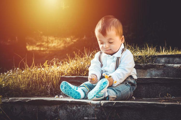 Full length of cute baby boy sitting on steps