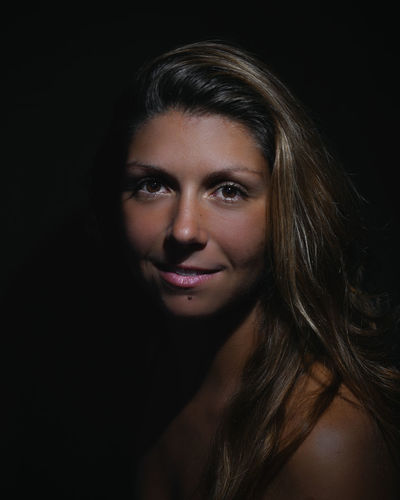 Portrait of a beautiful young woman over black background
