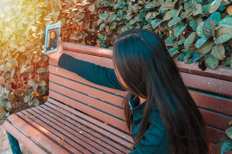 Lady taking selfie while sitting on a bench Park Selfie ✌ Smart Phone One Person People Long Hair Teenager Adult Only Women One Young Woman Only Young Adult Autumn Day Outdoors Young Women Leaf One Woman Only Adults Only Tree Nature