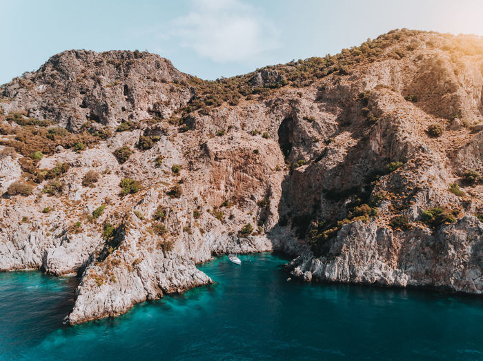 A sailing yacht tucked into dramatic cliffs inside of a secluded and beautiful turquoise bay in the summer. Drone  EyeEm Best Shots Holiday Mediterranean Sea The Week on EyeEm Aerial View Drone Photography Idyllic Outdoors Rock Formation Sailing Sailing Boat Sea Secluded  Tranquil Scene Turquoise Colored Vacation Water Yacht Yachting A New Beginning