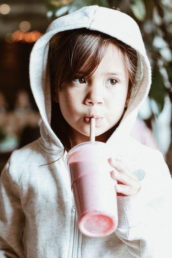 Portrait of cute girl drinking glass