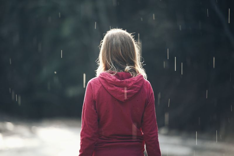 Rear view of girl standing in rain