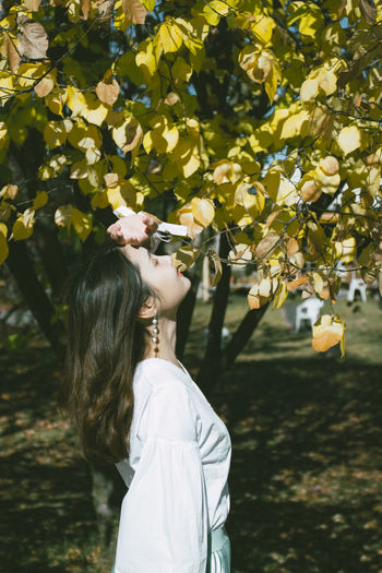 Side view of young woman with eyes closed standing by tree in park during sunny day