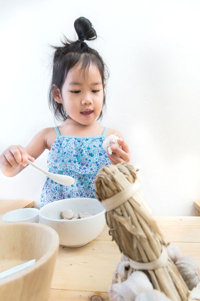 Black Hair Cheerful Childhood Cooking Cultures Cute Day Enjoyment Front View Girl Indoors  Kitchen Kitchen Utensils Looking Down One Person People Play Playing Portrait Sleeve  Smiling Top Knot White Background