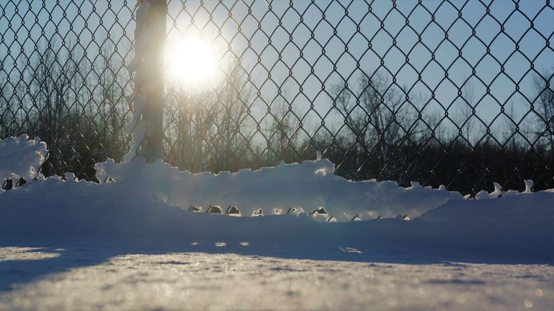 Snowy fence Beauty In Nature Close-up Cold Temperature Day Fence Lens Flare Nature No People Outdoors Sky Snow Sun Sunbeam Sunlight Water Winter