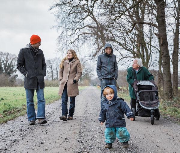 Full length of family walking on dirt road during winter