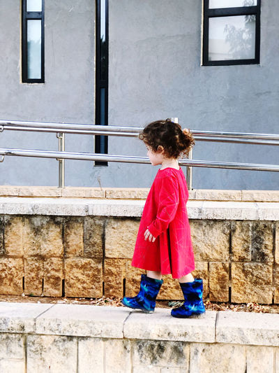 Side view of girl standing against staircase