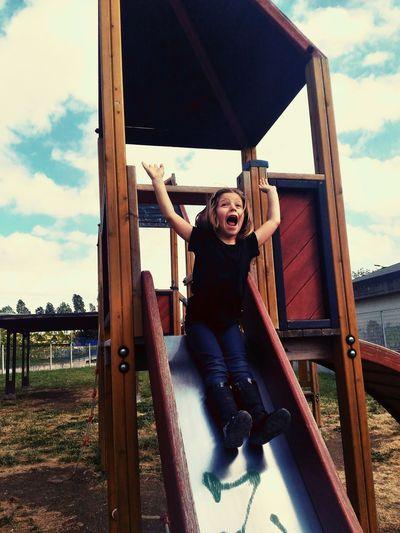 Full length of girl screaming on slide at playground