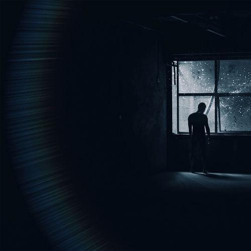 Silhouette woman standing in window