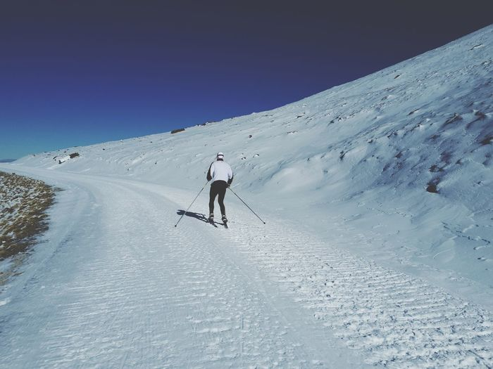 Rear view of man skiing on snowcapped mountain against clear sky