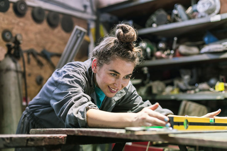 young woman working in a workshop Industry Measuring Mechanic Service Tomboy Uniform Apprentice Business Dirt Garage Headshot Indoors  Occupation One Person Overalls Portrait Repairing Skill  Small Business Smiling Tools Tough Work Tool Working Workshop