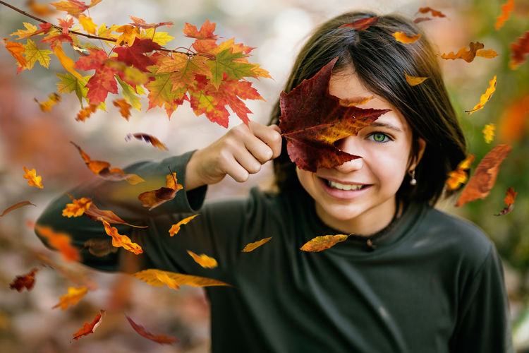 Portrait of cute girl holding autumn leaf outdoors