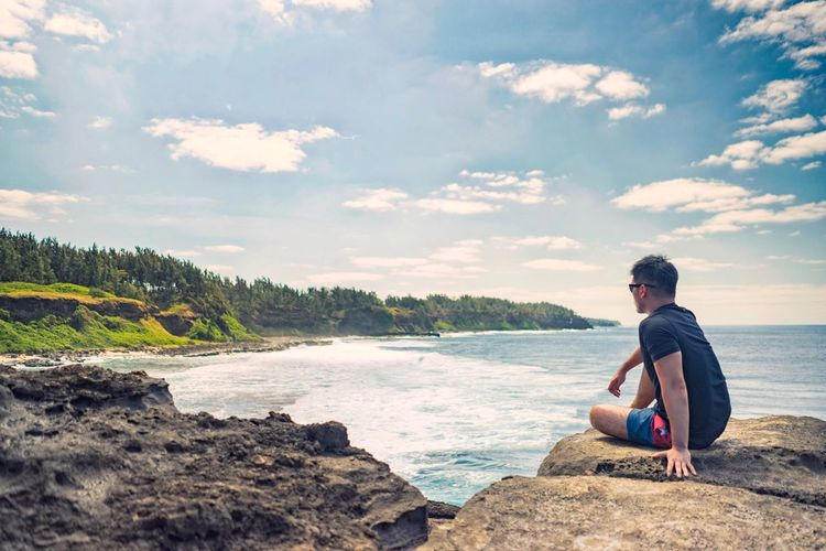 Man Sitting On Rocky Shore Against Blue Sky