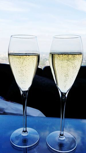 Close-Up Of Champagne Flutes On Table Against Sky