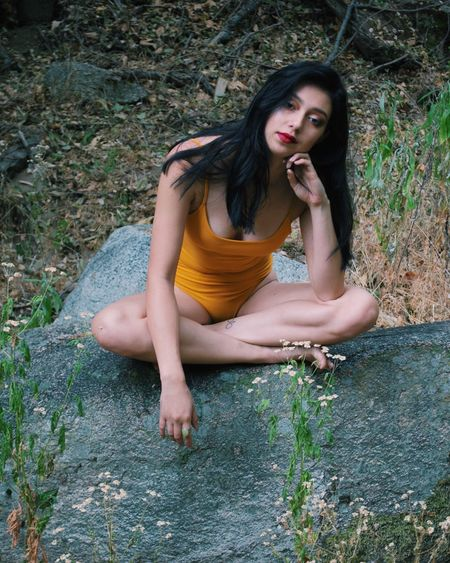 Beautiful young woman sitting in grass