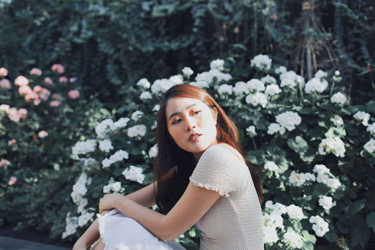 Beautiful young woman looking away while sitting against plants