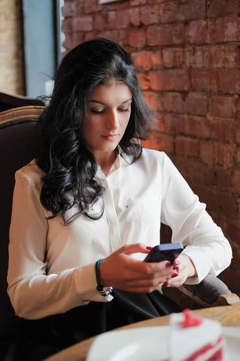 Businesswoman using mobile phone in restaurant
