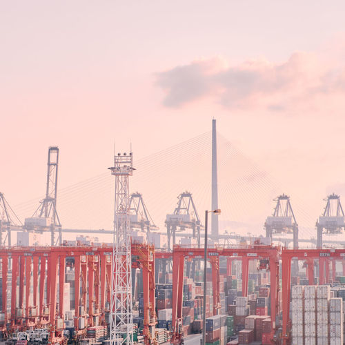 Cranes at harbor against sky during sunset