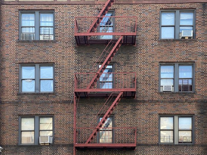 Low angle view of building red fire escape red bricks in mount vernon new york summer 2020