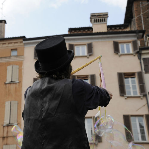 Rear view of man holding bubble wand against building