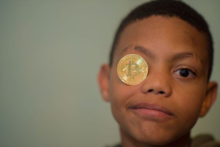 Close-Up Portrait Of Boy With Bitcoin On Eye Against Wall