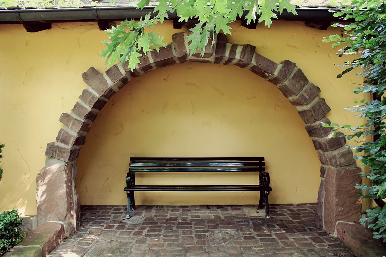 Empty Bench By Arch Wall