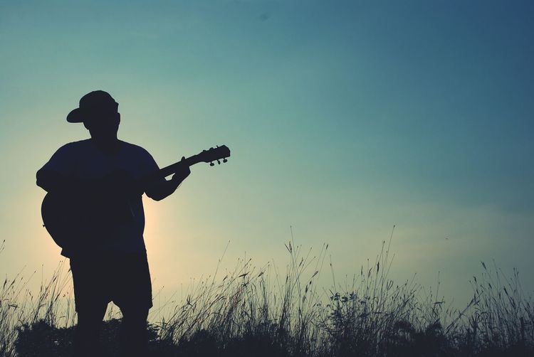 Silhouette man playing guitar while standing on field against sky