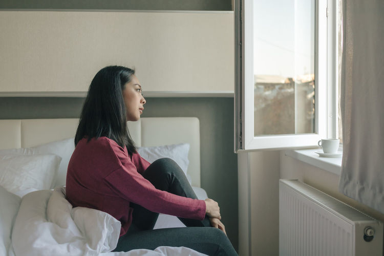 Woman looking away while sitting on bed at home
